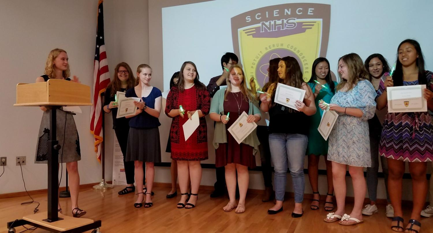 The Science National Honor Society members display their awards after being inducted as  Junior Hallie Trial, president, applauds the new members.
