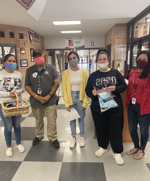 NHS seniors Rosa Navejas, Alicia Flores, and Gracelyn Caudle pose with Security Officer, Miguel Rodriguez, and FBHS receptionist, Melody Vega, after swapping their disposable masks for reusable ones.